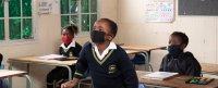 Three children wearing masks go back to school